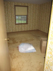 Bedroom with old carpet over hardwood floors
