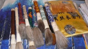 a bunch of antique chinese brushes and a silk scarf