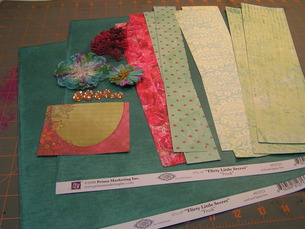 Beginning Supplies: 2 Sheets of patterned paper, an array of paper scraps cut into strips, a journal spot, flowers, lace, and gems
